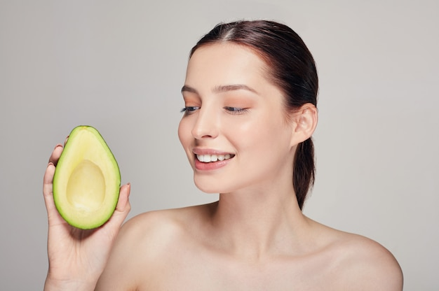 アボカドと純粋な輝きの肌を持つ魅力的な幸せで陽気な女性