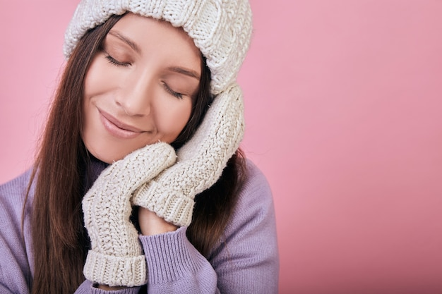Женщина с закрытыми глазами и сложив руки в варежки под щекой