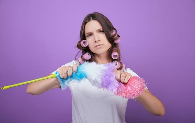邪悪な茶色の髪の女性がほこりのブラシを壊します。