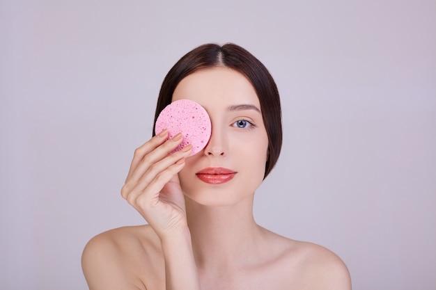 彼女の顔の近くにピンクのスポンジを保持している女性。