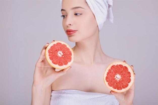 きれいな肌を持つ若い魅力的な女性は、彼女の手で新鮮なカットグレープフルーツを保持しています。