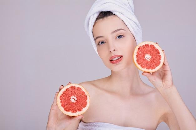 顔の近くのグレープフルーツを持つ女性の美しさの肖像画。