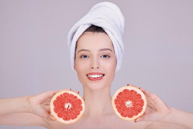 彼女の頭の上の白いタオルで笑顔の女性は、彼女の顔の近くにカットグレープフルーツを保持しています。