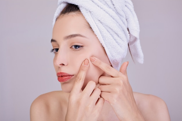 若い美しい女性は、頬ににきびを押します。