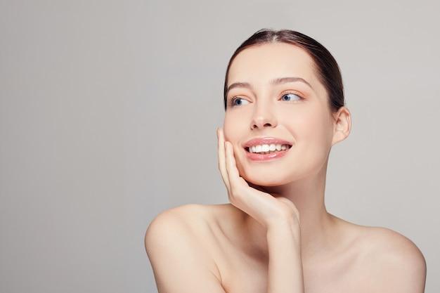 清潔で新鮮な肌、青い目と暗いと美しい若い女性が笑顔を聞く