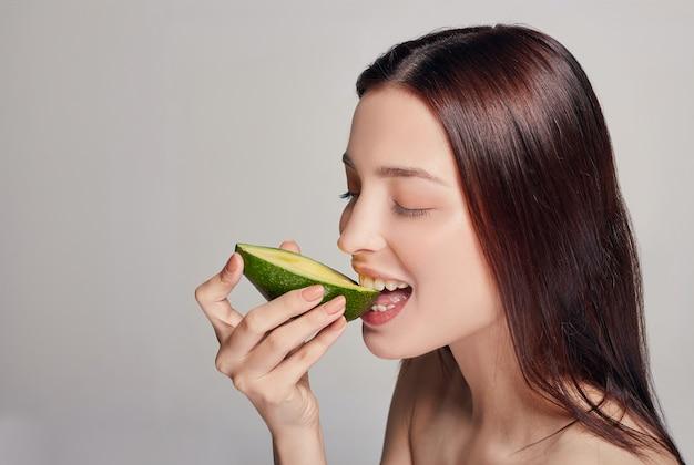 アボカドを食べる優しい茶色の髪の女性