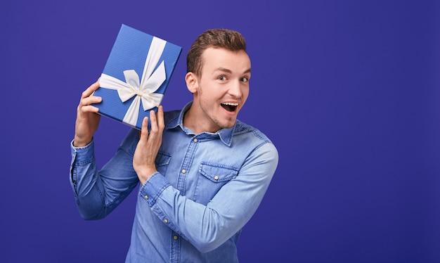 Радостный удивленный мужчина с темными волосами слушает, что гремит в подарок.