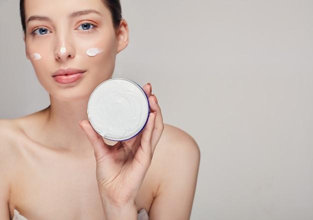 美しい女性が彼女の顔にクリームを適用します。完璧な肌を持つ女性の写真。スキンケアと美容のコンセプト。保湿クリーム