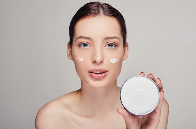 彼女の顔に保湿クリームを適用する若い美しい女性。完璧な肌を持つ若い女性の写真。