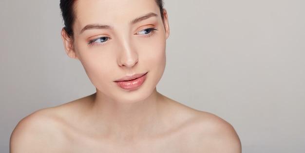 青い目と側を見てわずかな笑顔で完全な唇を持つ若い洗練された女性。グレー。黒髪。コピースペース。
