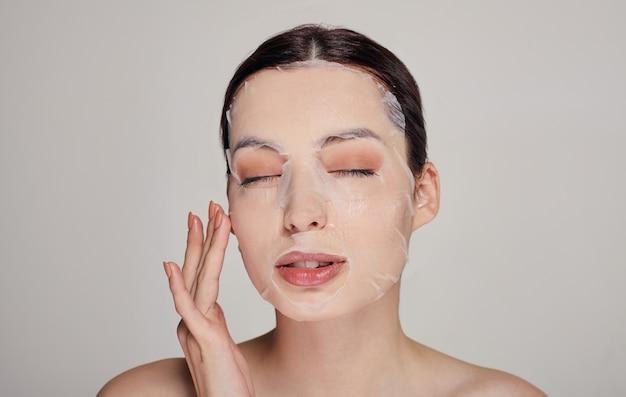 目を閉じて、保湿フェイスマスクと完全な唇を持つ若い美しい柔らかい女性。グレー。見下ろす。コピースペース。スパ、美容。