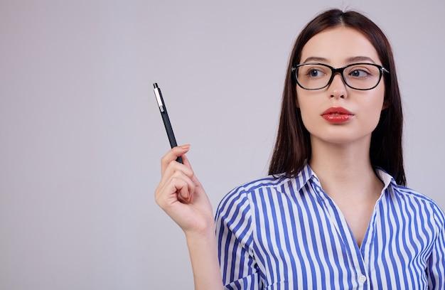 で、茶色の髪とメガネで快適な若いビジネス女性です。女性は彼女の手に黒のペンを保持し、側に見える