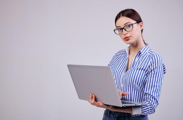 メガネとラップトップでストライプホワイトブルーシャツの女性管理者の写真