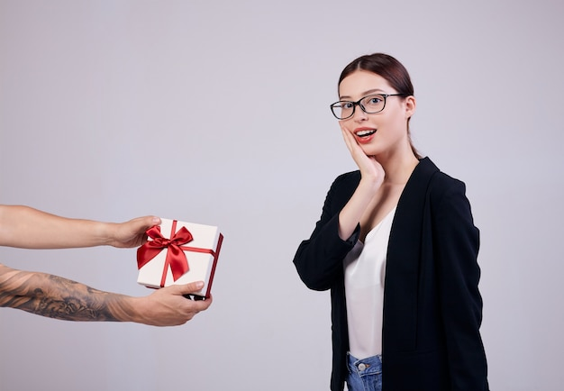 Приятно выглядящая деловая женщина стоит на сером в черном пиджаке, белой футболке и компьютерных очках. минута счастья.