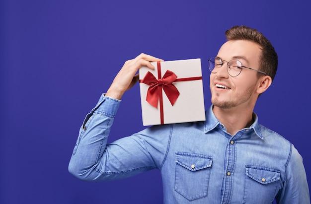 Улыбающийся молодой парень в джинсовой рубашке с подарком с в руке. рождество, новый год, день святого валентина.