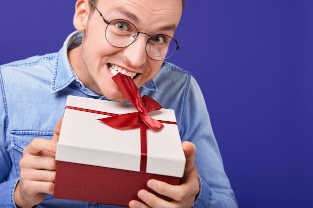 Веселый молодой парень в круглых очках стоит с подарком