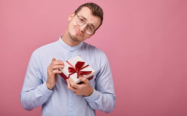 Удивленный мужчина в синей рубашке с черными очками держит в руках подарок