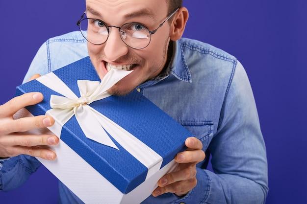 Веселый улыбающийся парень в круглых очках пытается развязать подарок зубами