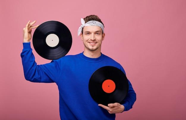 レトロなスタイルの白いバンダンホールドでヒッピー男の笑みを浮かべて黒のビニールレコードを胸のレベルで手に