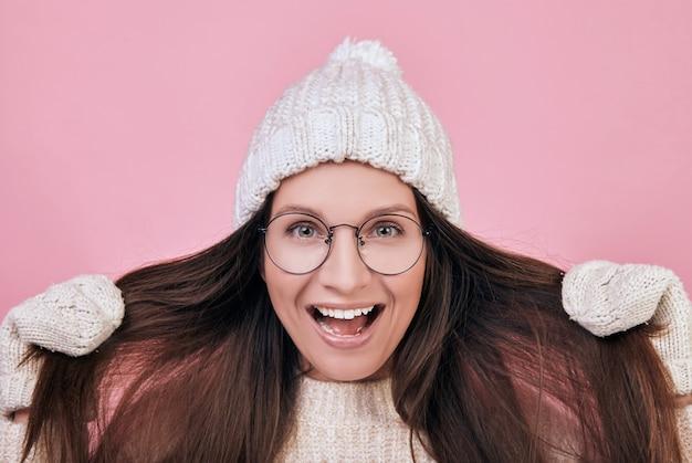 Веселая улыбающаяся девушка одета в теплый вязаный свитер и шапку