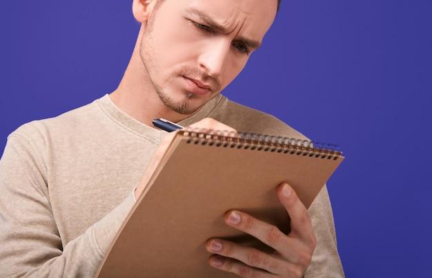 Концентрированный автор пишет план действий или решает проблему в бумажной тетради