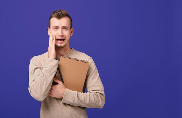 Молодой испуганный студент держит руку за рот, открывая рот и кричит