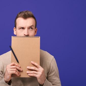ハンサムな男は茶色のノートを保持しています。