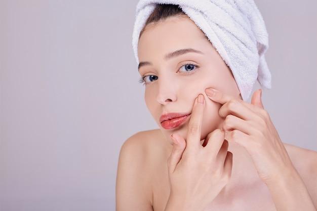 Молодая женщина очищает поры на щеке.