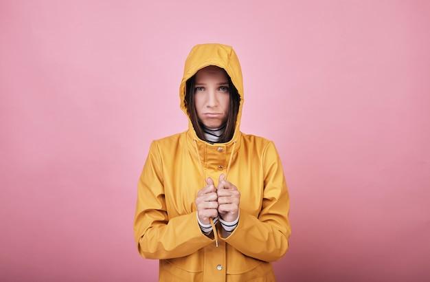 黄色のレインコートで穏やかな悲しい女性が落ち着いてフレームに見える