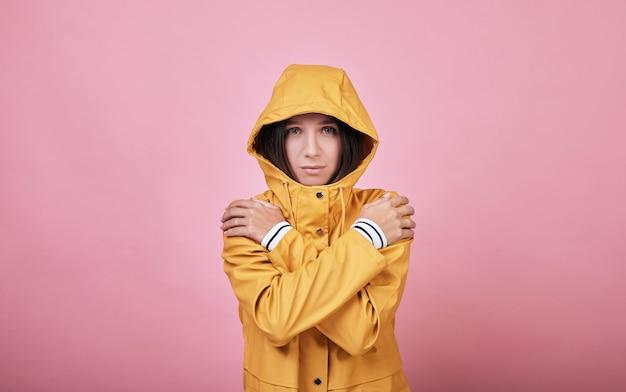フード付きのクールな魅力的な悲しい女性のレインコートは凍っていて震えています
