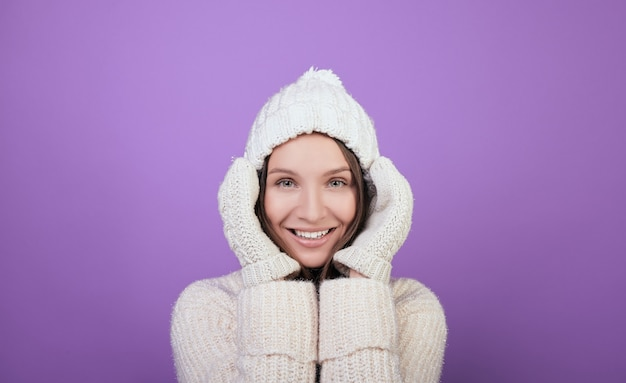 冬の白いニット帽子と白いミトンに緑の目を持つ魅力的な女性