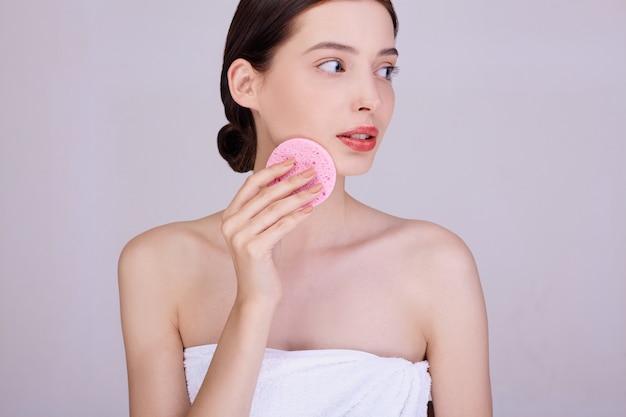 若いブルネットの女性が化粧から彼女の顔を浄化します