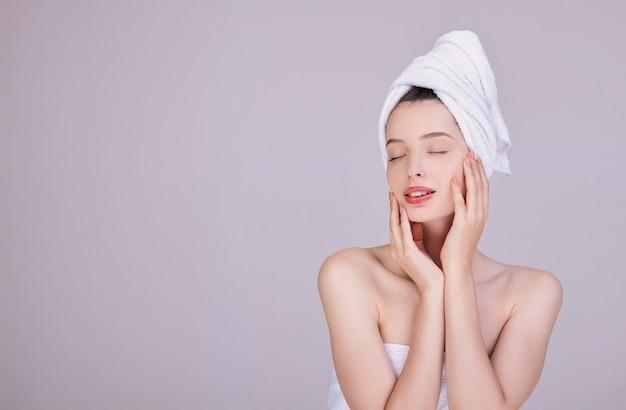 白いタオルで官能的なブルネットは彼女の顔に触れる