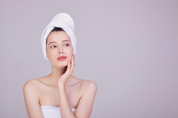 Молодая женщина с полотенцем на голове, трогает ее лицо