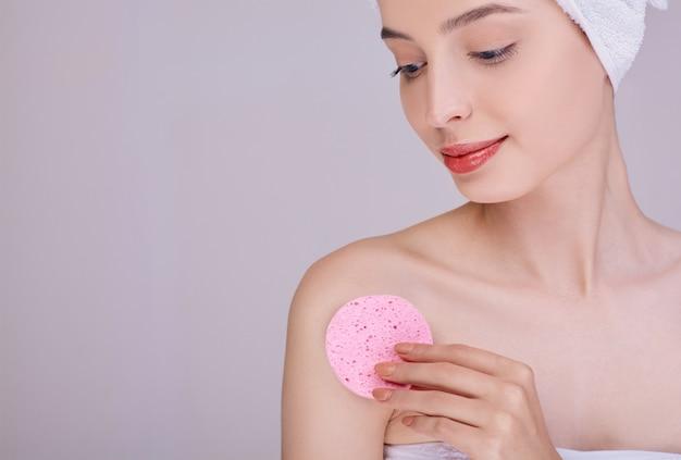 女性はピンクのスポンジで彼女の体をきれいにします