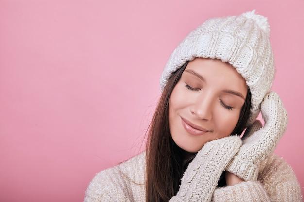 Девушка с закрытыми глазами в свитере, шапке и варежках