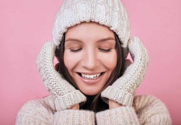 Мило улыбается женщина с закрытыми глазами в вязаной шапке