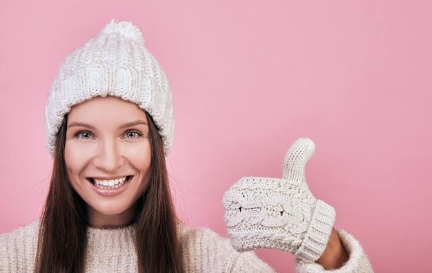 Милая девушка с зелеными глазами улыбается и показывает большой палец вверх