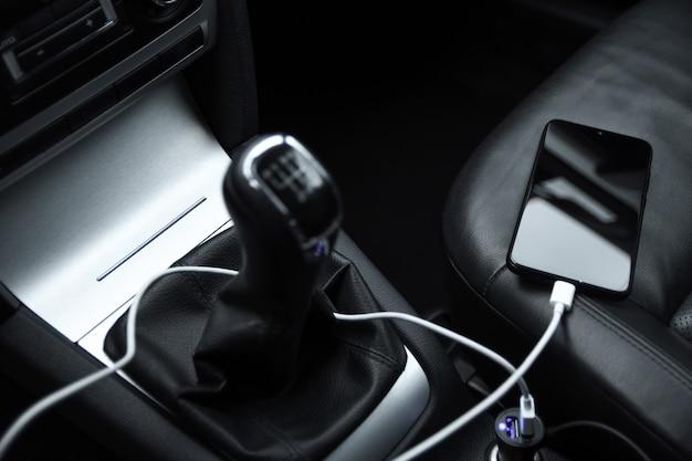 Мобильный телефон, зарядка аккумулятора смартфона, зарядка в автомобильной вилке крупным планом