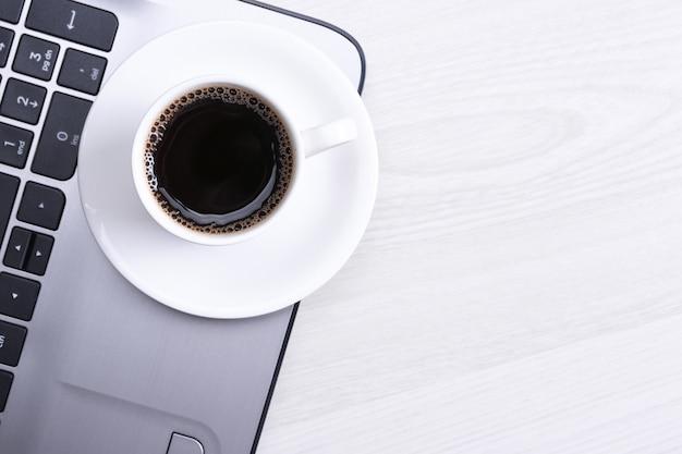 木製のデスクテーブルの上のノートパソコンのキーボードのコーヒーカップ。平面図、フラットレイアウト。警官