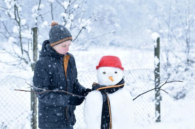 Мальчик делает снеговика, веселые зимние мероприятия