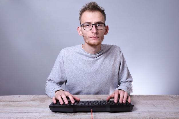 Смешной компьютерщик молодой человек, работающий на компьютере. типирование на клавиатуре программист в очках перед компьютером.