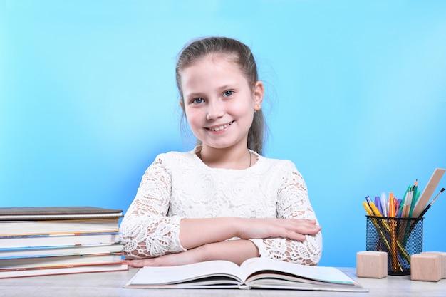 Обратно в школу. счастливый милый трудолюбивый ребенок сидит за столом в помещении. малыш учится в классе.карантин.кид учится дома.