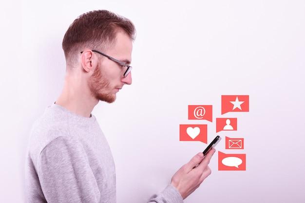 Молодой человек, глядя на телефон для активности и количество лайков, подписчиков и комментариев.