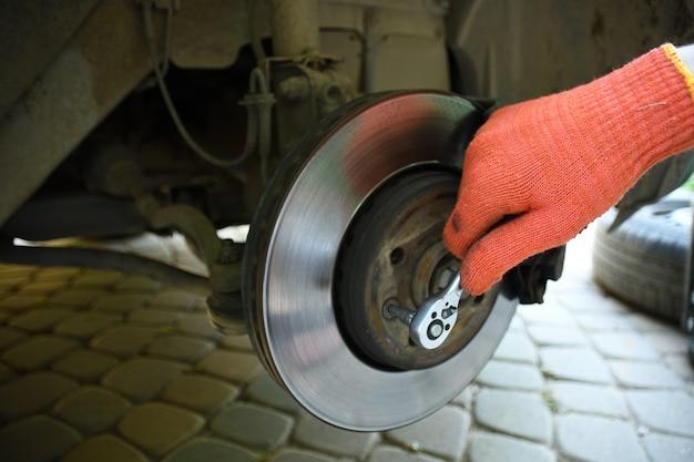 Автомеханик ремонтирует подвеску поднятого автомобиля на станции авторемонтного цеха