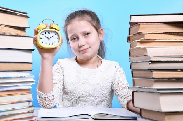 Обратно в школу. счастливый милый трудолюбивый ребенок сидит за столом в помещении. малыш учится в классе, учится дома. горы из книг по бокам