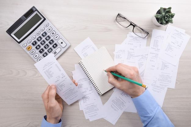 認識できないビジネスマンのデスクオフィスで電卓を使用して書くとホームオフィスでのコストについて計算でメモをとる。