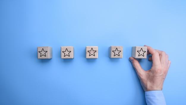 Мужской рукой положить пять деревянных нарезанных кубиков со звездочкой на них в ряд