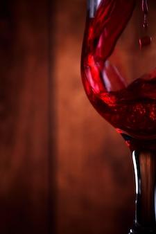 木製の素朴な背景に対してグラスに赤ワインを注ぐ