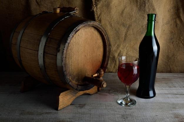 ガラスと木製の背景にコルク抜きでワインのボトル